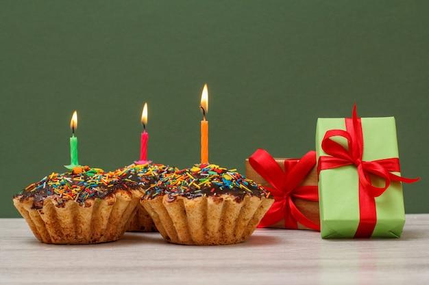 Tres deliciosos cupcakes de cumpleaños con glaseado de chocolate y caramelo, decorados con velas festivas encendidas y cajas de regalo sobre fondo verde. feliz cumpleaños concepto mínimo.