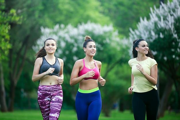 Tres deportistas alegres corriendo en el parque