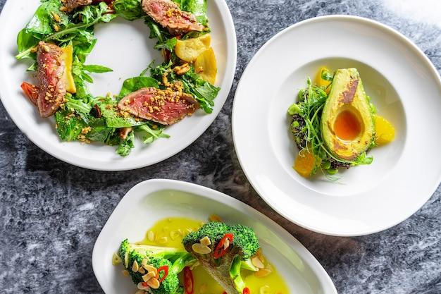 Tres diferentes ensaladas con tataki de ternera, aguacate a la parrilla y brócoli en plato blanco
