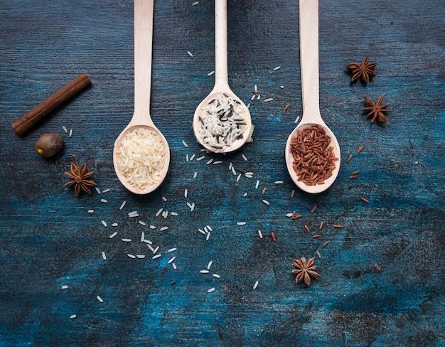 Tres diferentes tipos de arroz en cucharas en mesa