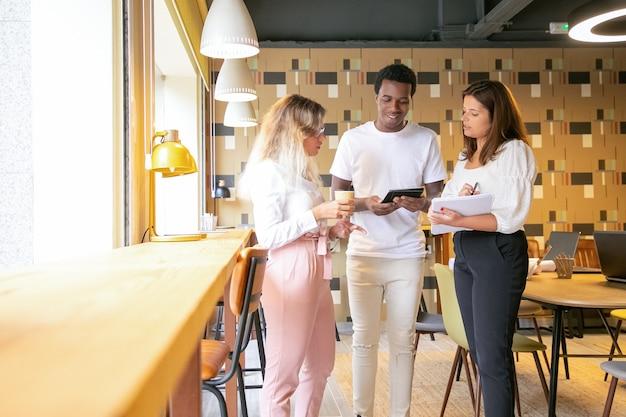 Tres diseñadores de contenido de pie en el interior y discutiendo el diseño