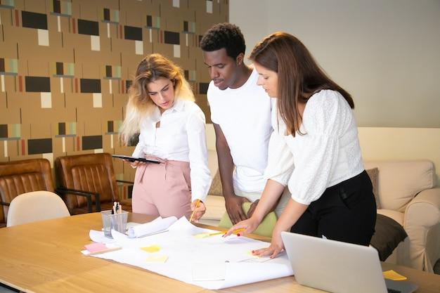 Tres diseñadores multiétnicos de pie y mirando el borrador