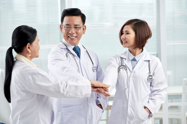Tres doctores dando gesto de unidad que simboliza el trabajo en equipo