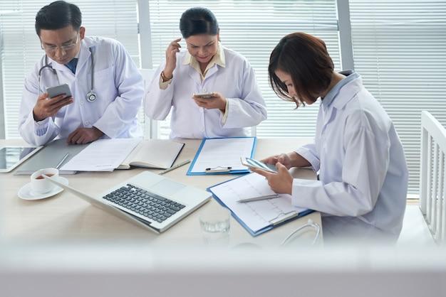 Tres doctores ocupados usando sus aparatos
