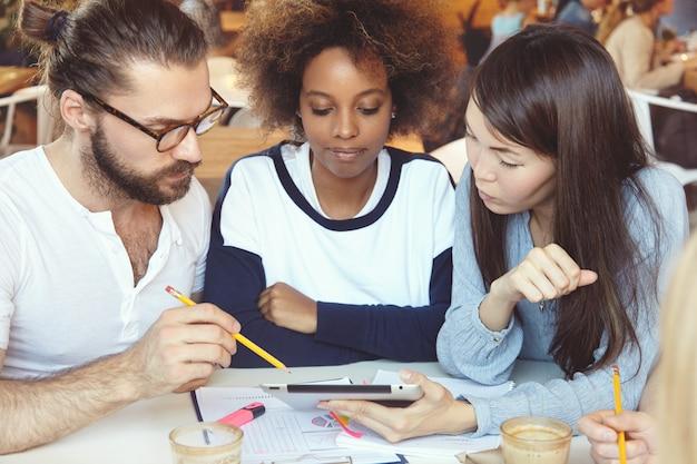 Tres empresarios ambiciosos que desarrollan la estrategia empresarial de su puesta en marcha.