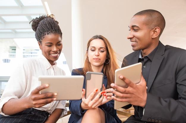 Tres empresarios felices usando gadgets en la oficina