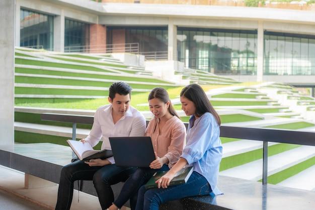 Tres estudiantes asiáticos están discutiendo sobre la preparación del examen, presentación, estudio, estudio para la preparación del examen con una computadora portátil en la universidad.