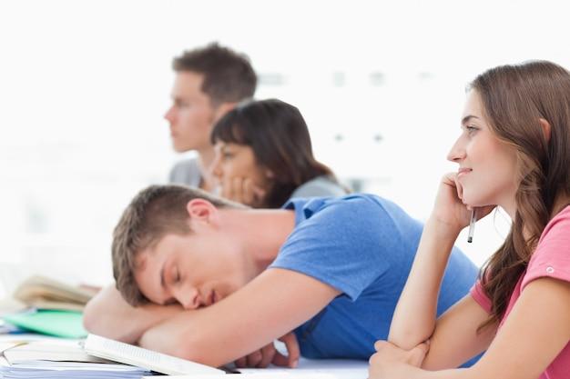 Tres estudiantes escuchando en clase con otro estudiante tomando una siesta