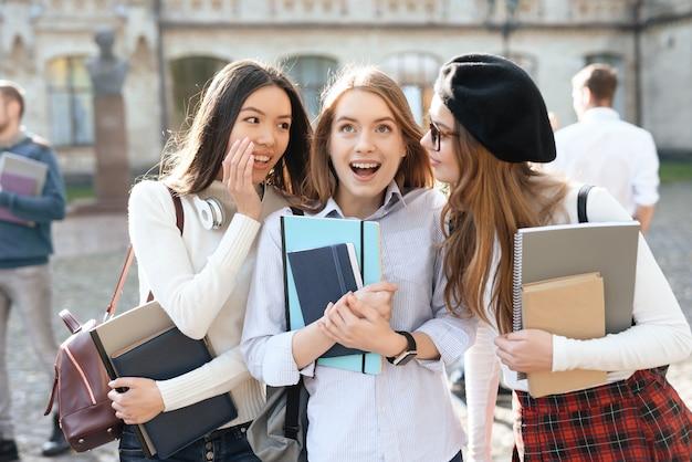 Tres estudiantes hacen selfie en el patio de la universidad.