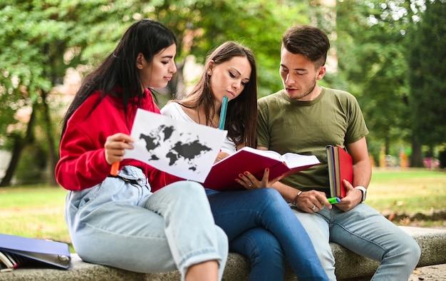 Tres estudiantes que estudian juntos sentados en un banco al aire libre