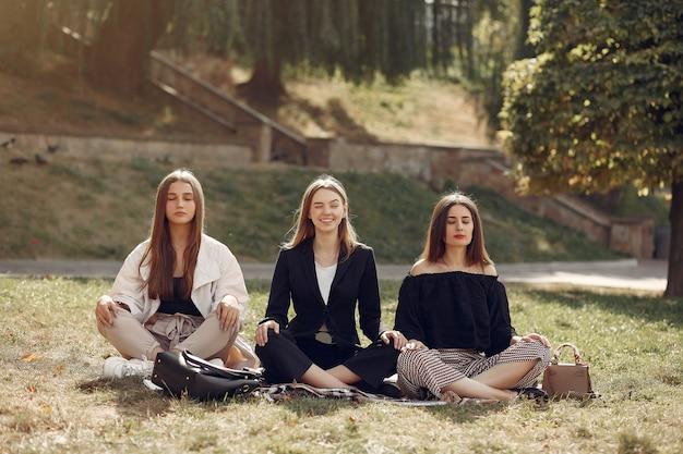 Tres estudiantes sentados en un pasto con laptop