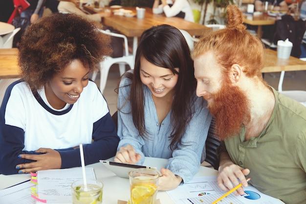 Tres estudiantes trabajando juntos en la tarea del hogar, sentados en la cafetería, investigando, navegando por internet, usando wi-fi en el panel táctil.