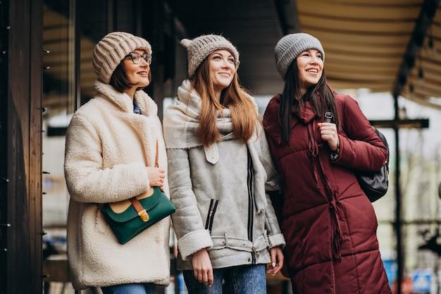 Tres estudiantes en traje de invierno en la calle