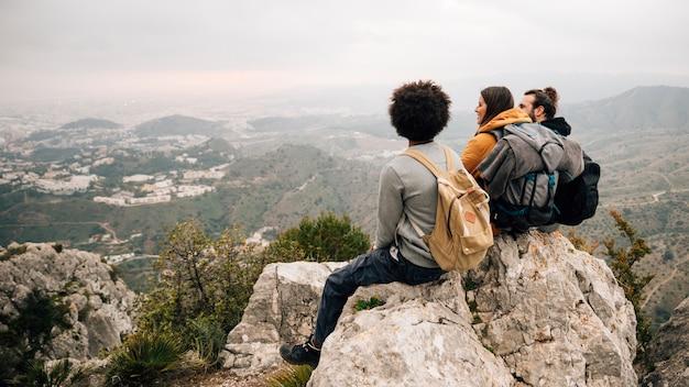 Tres excursionistas hombres y mujeres sentados en la cima de la roca con vistas al paisaje urbano y la montaña