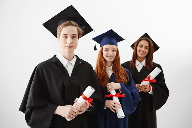 Tres felices graduados universitarios internacionales sonrientes regocijándose con diplomas. futuros abogados o ingenieros.