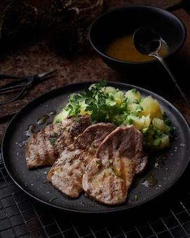 Tres filetes de lomo de cerdo a la parrilla sobre placa negra con lado de patatas hervidas, guisantes y perejil.