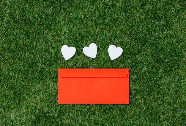 Tres formas de corazón y sobre rojo sobre la hierba verde.