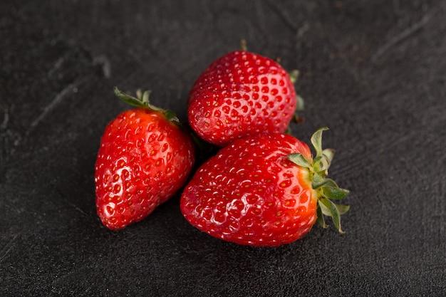 Tres fresas rojas suaves frescas aisladas sobre piso oscuro