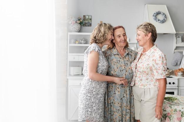 Tres generaciones mujeres juntas y sonrientes en casa.