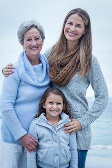 Tres generaciones de mujeres de pie en la playa