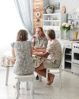 Tres generaciones de mujeres tomando café juntas en la cocina.
