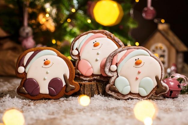 Tres gingerbread feliz sentado muñeco de nieve o bola de nieve en una acogedora decoración cálida con luces de guirnalda
