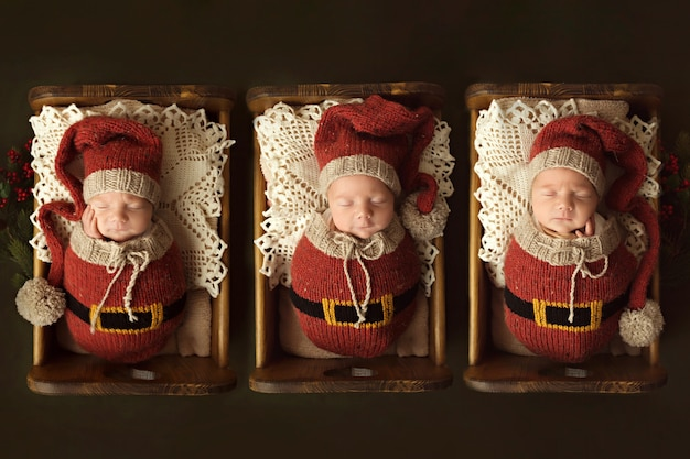 Tres hermanos recién nacidos duermen en cunas vestidos de duendes. foto de alta calidad