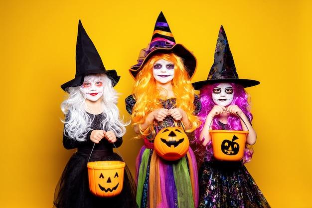 Tres hermosa niña en un traje de bruja asustando y haciendo muecas