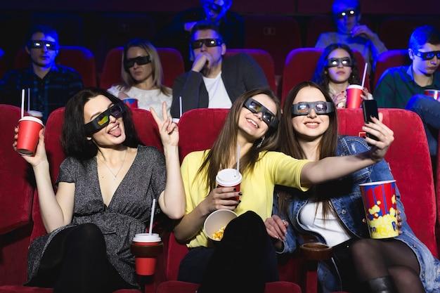 Tres hermosas amigas riendo felices haciendo una selfie juntos durante una película en el cine