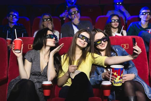 Tres hermosas amigas riendo felizmente haciendo un selfie juntos durante una película en el cine
