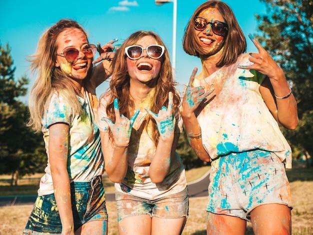 Tres hermosas chicas felices haciendo fiesta en el festival de colores holi