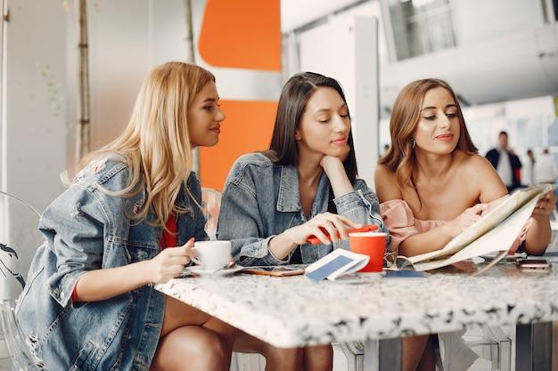 Tres hermosas chicas sentadas en el aeropuerto