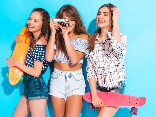 Tres hermosas chicas sonrientes con estilo con coloridas patinetas de centavo. mujeres en ropa de camisa a cuadros de verano. tomar fotos en la cámara de fotos retro