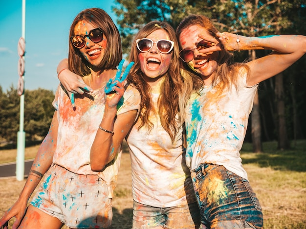 Tres hermosas chicas sonrientes posando en la fiesta de holi