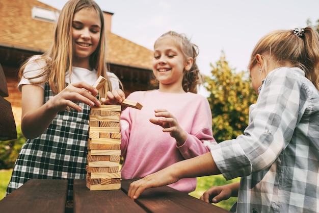 Tres hermosas hermanas jugando un juego de mesa de madera al aire libre cerca de su casa