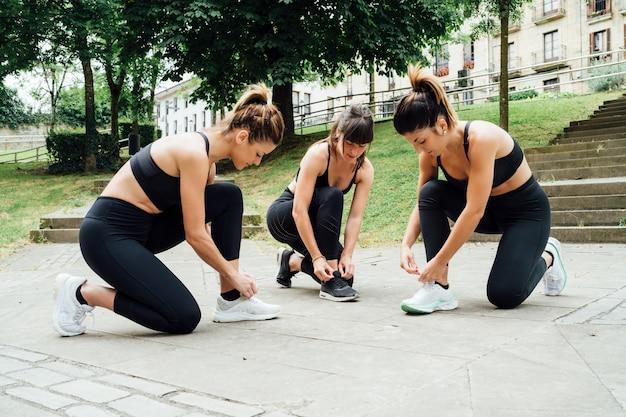Tres hermosas mujeres atarse los cordones de los zapatos antes de salir a correr en un parque de la ciudad