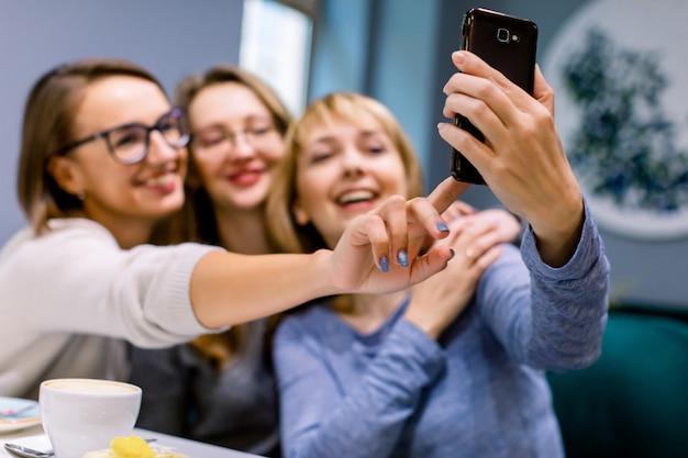 Tres hermosas mujeres caucásicas tomando selfie en café en el interior, reunión de mejores amigos
