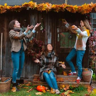 Tres hermosas mujeres jóvenes, alegremente lanzando una hoja de otoño amarilla, sonriendo sobre un fondo de madera vieja. la temporada de moda de otoño.