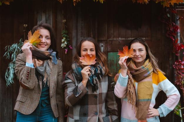 Tres hermosas mujeres jóvenes, cubriendo sus rostros con una hoja de otoño amarilla, sonriendo sobre un fondo de madera vieja. la temporada de moda de otoño.