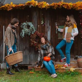 Tres hermosas mujeres jóvenes, divirtiéndose con una hoja de otoño amarilla, sonriendo sobre un fondo de madera vieja. la temporada de moda de otoño.
