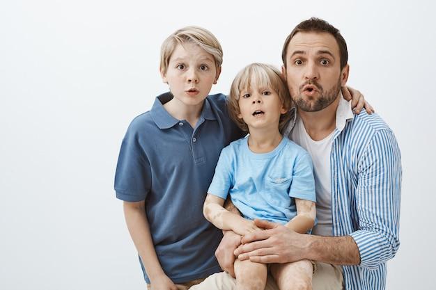 Tres hermosos miembros de la familia de pie sobre una pared gris, haciendo expresiones de sorpresa y asombro mientras se abrazan