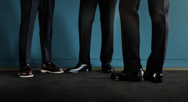 Tres hombre de negocios de pie junto a la pared. socios comerciales o trabajo en equipo hablando juntos