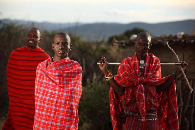 Tres hombres africanos con mantas rojas envueltas alrededor de ellos