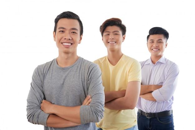 Tres hombres asiáticos de pie en fila con los brazos cruzados y sonriendo a la cámara