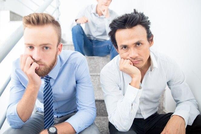 Tres hombres de negocios aburridos sentado en las escaleras