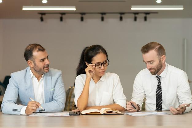 Tres hombres de negocios serios que trabajan con documentos en el escritorio