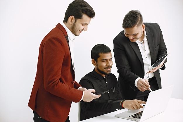 Tres hombres discutiendo ideas. pared blanca. nacionalidad india.