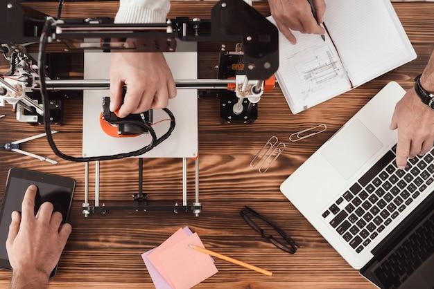 Tres hombres están trabajando en la creación de una impresora 3d.