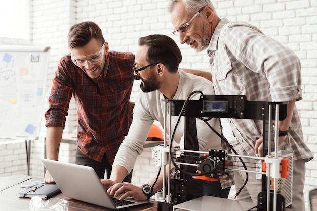 Tres hombres están trabajando en la preparación de una impresora 3d para imprimir.