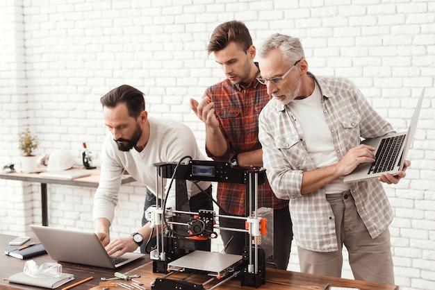 Tres hombres están trabajando en la preparación de una impresora 3d.